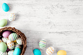 Pastel colored Easter eggs on white rustic background.