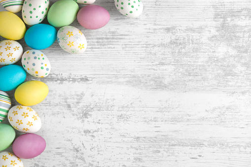 Multi colored Easter eggs on white rustic background.