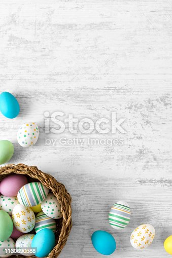 Colorful easter eggs in wicker on white rustic background