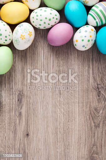 Pastel colored easter eggs on wooden table background.