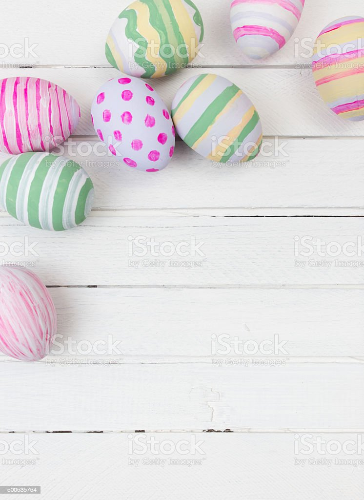 Easter eggs painted in pastel colors on a white wood stock photo