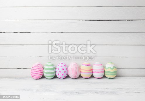 istock Easter eggs painted in pastel colors on white wooden background. 499233334