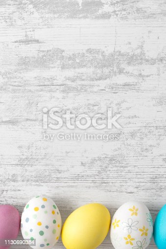 Easter eggs painted in pastel colors on white wooden background with copy space