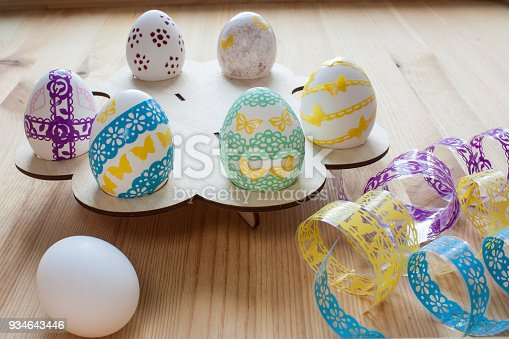 istock Easter eggs painted on a wooden stand, front view 934643446