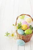 colorful easter eggs and spring flowers in basket