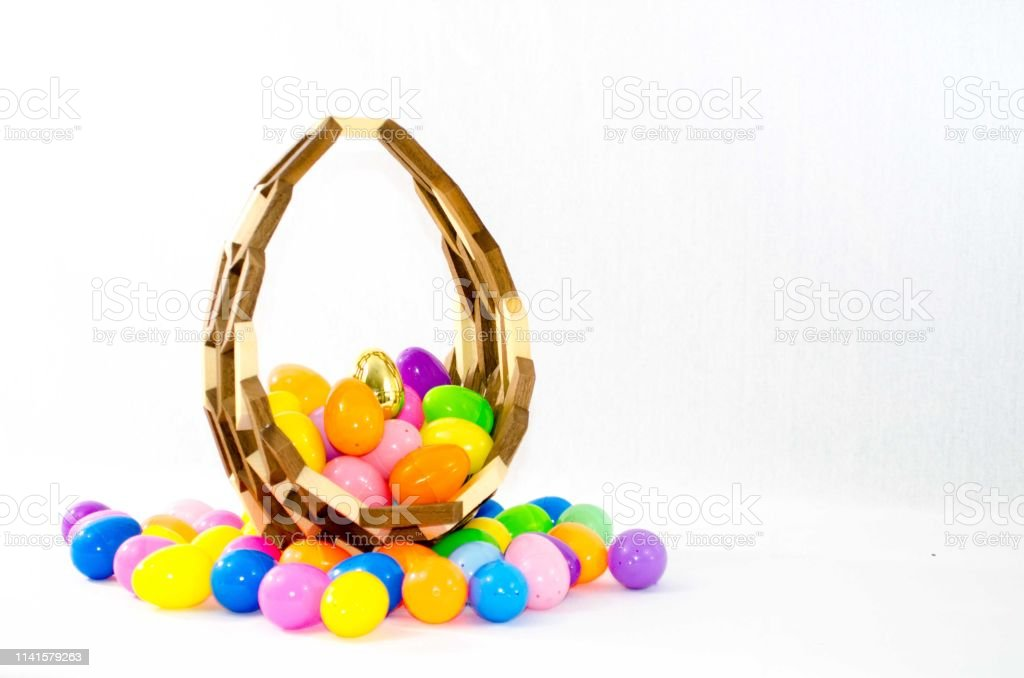 Easter eggs sit in a wooden hand made basket stock photo