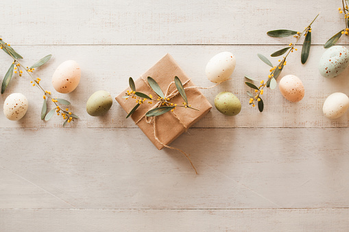 White wooden table with  pastel colored Easter eggs, fresh garden flowers and brown paper wrapped gift