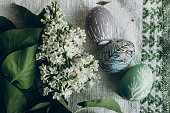 easter eggs with floral and chick ornaments on rustic background with lilac flowers. top view. space for text. happy easter. greeting card concept. stylish decoration