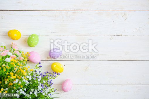 istock Easter eggs with flowers on white old wooden background 922411134