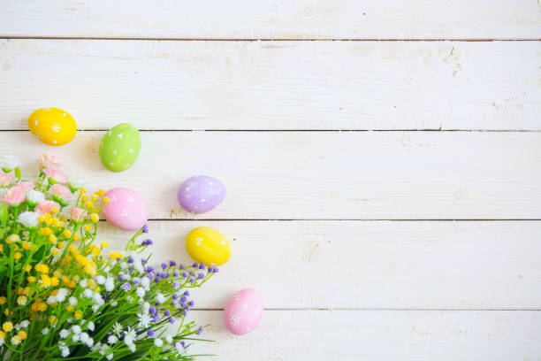 Easter eggs with flowers on white old wooden background stock photo
