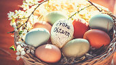 """Easter egg with German lettering """"Happy Easter"""" and other natural chicken eggs in the nest of grass"""
