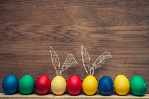 Easter eggs with rabbit ears on a wooden background textures