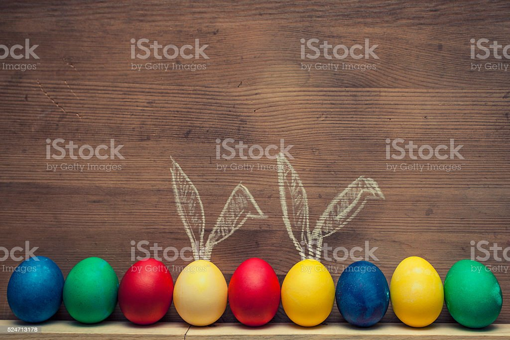 Easter eggs with rabbit ears on a wooden background textures stock photo