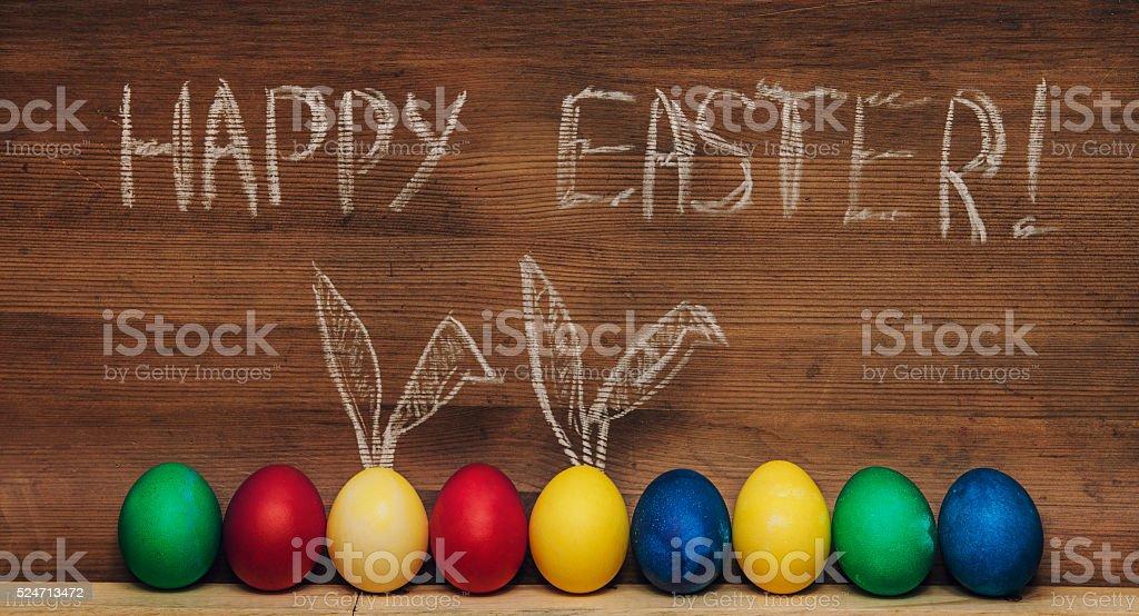 Huevos de Pascua con orejas de conejo sobre un fondo de madera y texturas - foto de stock