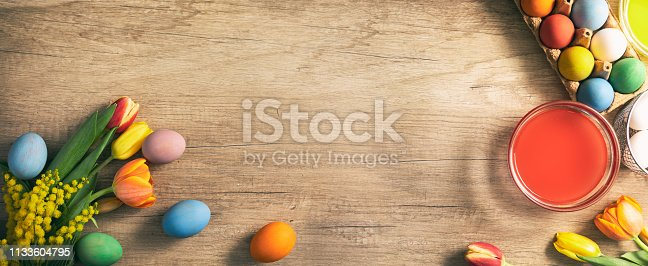922843504 istock photo Easter eggs with sprig flowers on wooden  table 1133604795