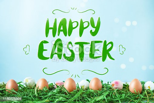 istock Easter eggs With the lettering Happy Easter on green grass, tulips with bokeh and sunlight on a blue background 1130775304