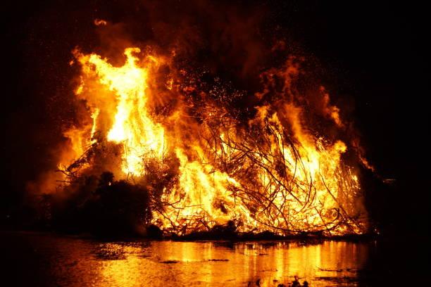 osterfeuer am ufer eines sees - osterfeuer stock-fotos und bilder