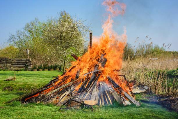 osterfeuer auf der wiese im frühling - osterfeuer stock-fotos und bilder