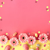 Easter flat lay in yellow and coral colors with painted eggs and gerbera daisy flowers, copy-space, square composition.