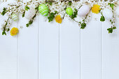 Easter decoration with spring flowers and eggs on white planks.