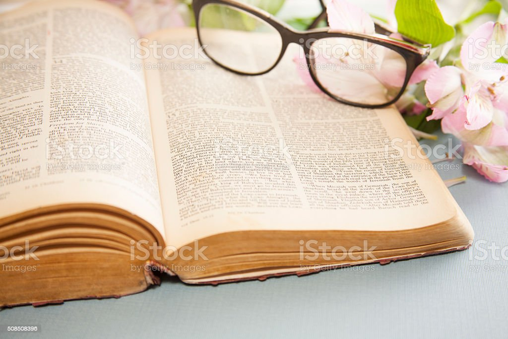 Easter. Flowers and glasses on open Bible. stock photo