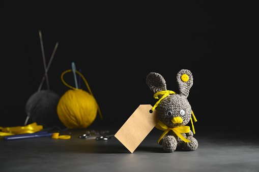 DIY Easter gift making theme. Handmade knitted toy Easter rabbit with tag, and needlework accessories. Black backdrop. Knitting concept. Dark moody style, Selective focus