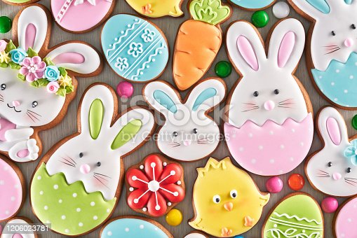 From above view of colorful ginger glazed cookies and chocolate balls isolated on wooden background. Close up of homemade lovely delicious pastry in shape of easter animals, eggs, flowers and carrots.