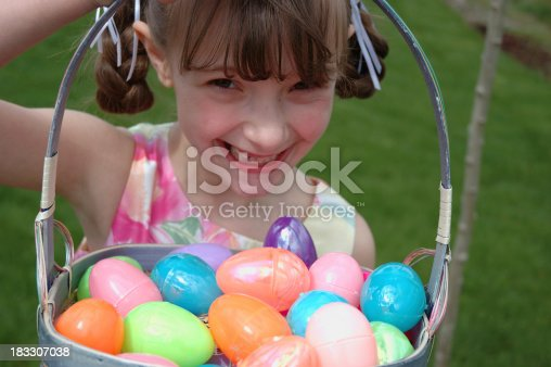 A smiling young girl holding an Easter basket full of colorful eggs.