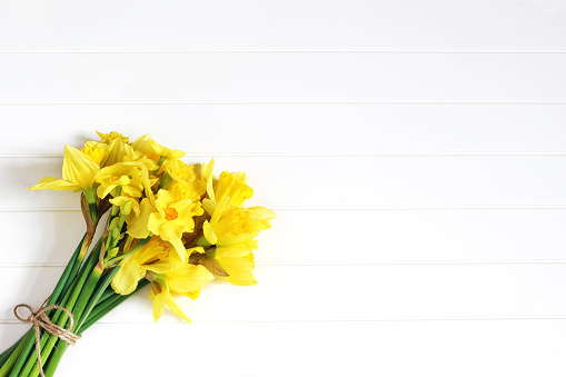 Easter greeting card, invitation. Bouquet of yellow daffodils, narcissus flowers lying on white wooden table. Spring concept. Feminine styled stock photo, floral composition. Flat lay, top view.