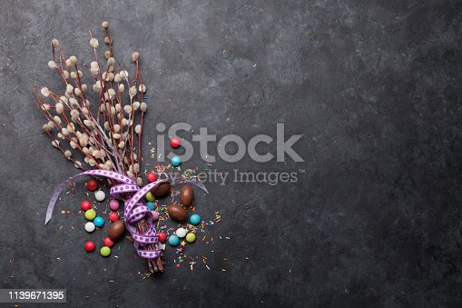 Easter greeting card with chocolate eggs and colorful candies. Top view on stone table with space for your greetings
