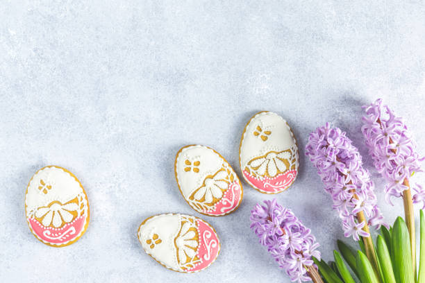 Easter greeting card with colored pink gingerbread eggs near hyacinths over light gray concrete surface background. Happy Easter stock photo
