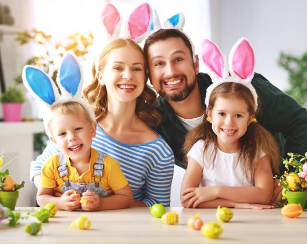 Ostern. Glückliche Familienmutter Vater und Kinder bereiten sich auf Ferienhaus mit Eiern vor – Foto