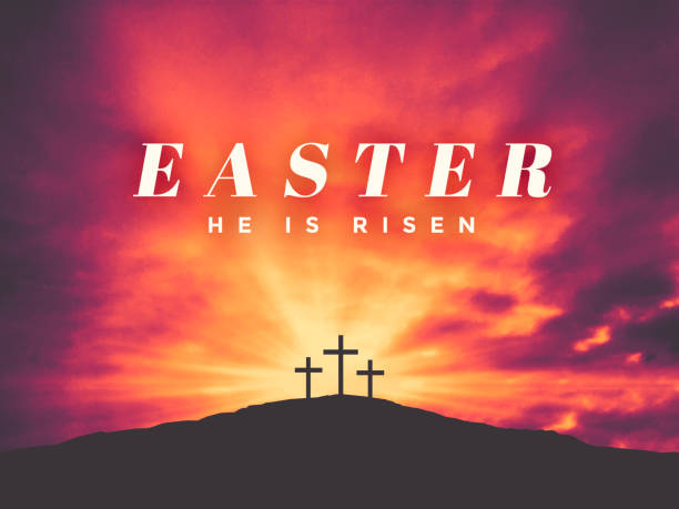 Easter He Is Risen Text with Three Christian Crosses on Hill of Calvary with Colorful Clouds in Sky stock photo