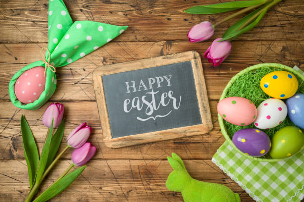 Easter holiday background with chalkboard, easter eggs in basket and tulip flowers on wooden table. stock photo