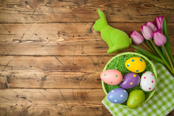 Easter holiday background with easter eggs in basket and tulip flowers on wooden table. stock photo