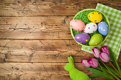 Easter holiday background with easter eggs in basket and tulip flowers on wooden table.
