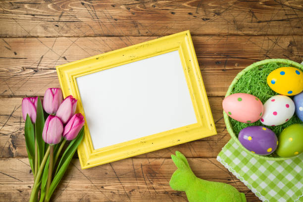 Easter holiday background with photo frame; easter eggs in basket and tulip flowers on wooden table. stock photo