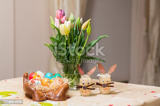 921112244 istock photo Easter holiday with colored eggs and flowers. colorful tulips near the painted Easter eggs of different colors 1218854836