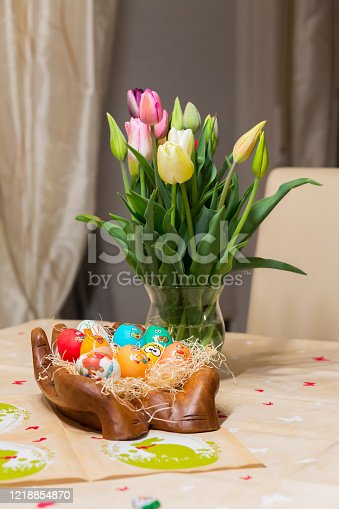 921112244 istock photo Easter holiday with colored eggs and flowers. colorful tulips near the painted Easter eggs of different colors 1218854870