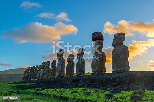 The sun shining at sunrise on the fifteen Moai of the Easter Island in the Pacific Ocean, Chile.
