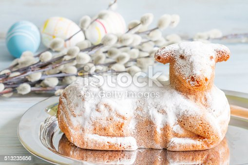 istock Easter lamb cake eggs and catkins on blue background 513235656