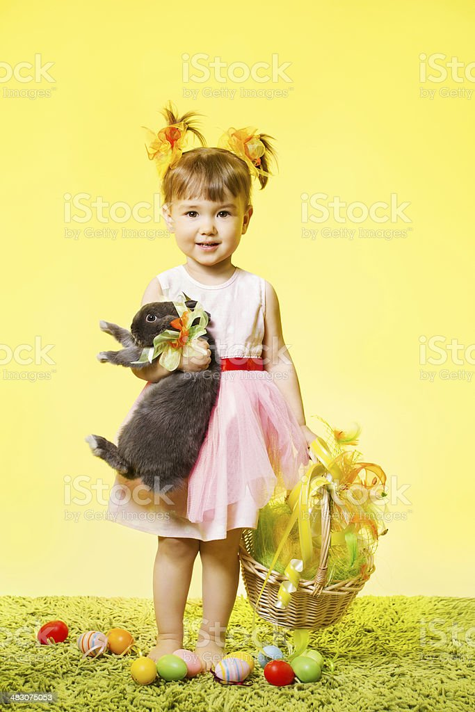 easter little girl, kid holding bunny rabbit basket eggs stock photo