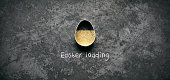 Easter loading concept. Egg shaped pastry cutter and golden glitter on old metal