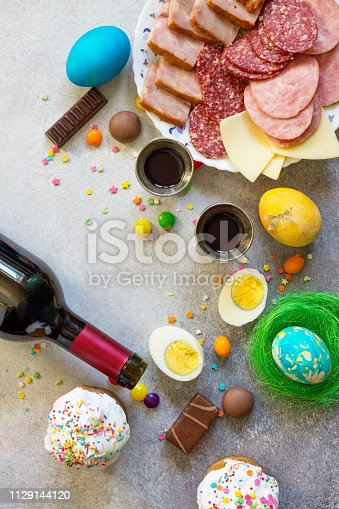 istock Easter meal Breakfast. Easter cake, painted eggs, red wine (Cahors) and delicious delicatessen on table. Top view flat lay background. Copy space. 1129144120