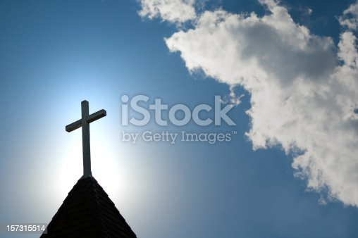 A wood cross on an old church steeple backlighted by a rising sun. Some copy space.