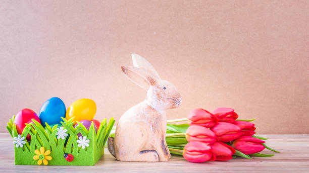 Easter nest with colourful Easter eggs, Easter bunny and red tulips Osternest mit bunte Ostereier, Osterhase und rote Tulpen vor einem Holz Hintergrund osterhase stock pictures, royalty-free photos & images