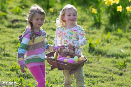 Two little girls walk through a field of daffodiles with a basket of easter eggs.