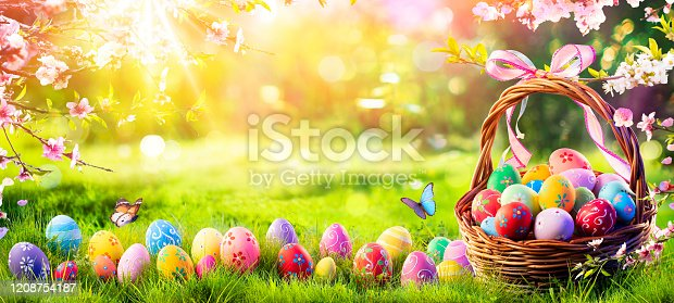 istock Easter - Painted Eggs In Basket On Grass In Sunny Orchard 1208754187