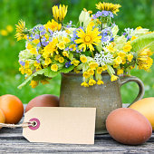 Bouquet with spring flowers easter eggs and label