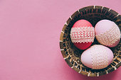 Cute easter dyed pink eggs covered with white lace in a cinnamon wooden plate on a pink background